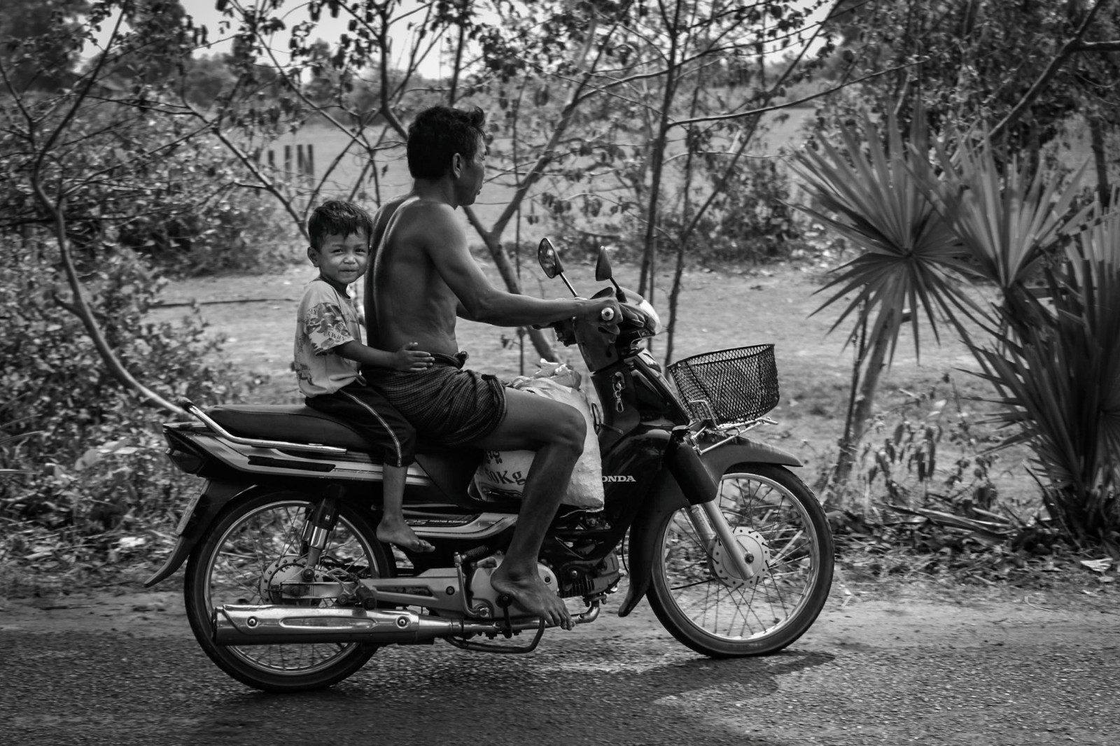 Cambodia photo tours Angkor Wat father and son on a motorbike