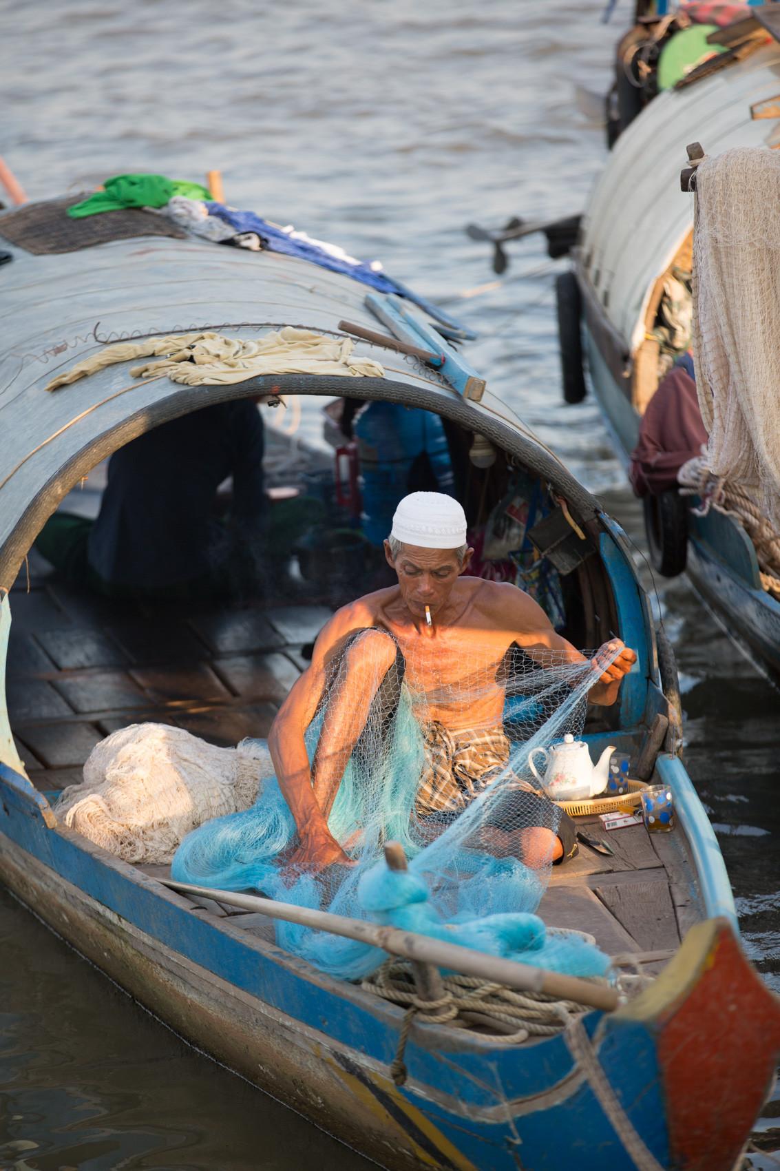 Cham man repairing fishing nets Phnom Penh